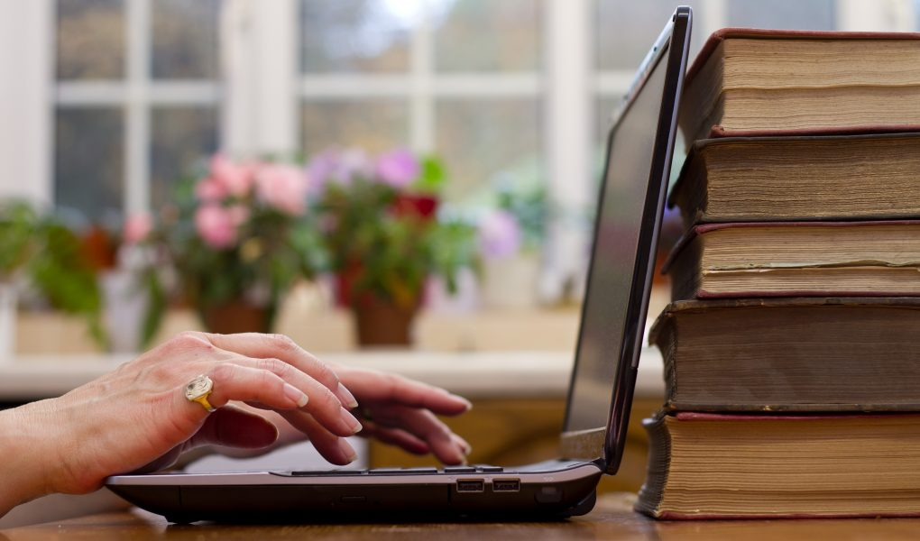 Hands typing at a laptop, with potted flowers in the background and a stack of books behind the laptop screen.