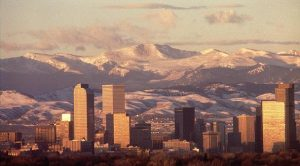 Denver skyline at sunset, with mountains behind