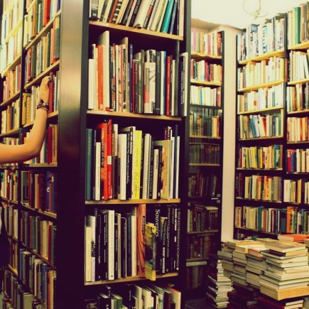 Young woman pulling a book off the shelf of a bookstore; the entire picture is dominated by bookshelves and books are stacked on the floor.
