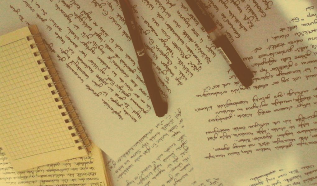 Scattered papers with handwriting, two pens on top